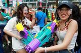 Люди стреляют из водных пистолетов во время празднования Сонгкрана — тайского Нового года в Бангкоке, Таиланд.