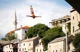 Участник традиционных соревнований по хай-дайвингу в Мостаре на юге Боснии прыгает в воду с 27-метровой высоты исторического Старого моста через Неретву.