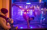 Представления цирковой компании Cirk La Putyka через витрину закрытого магазина в период действия ограничений во время пандемии COVID-19.