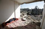 Палестинец в руинах своего дома, который был разрушен в результате авиаударов Израиля по сектору Газа.
